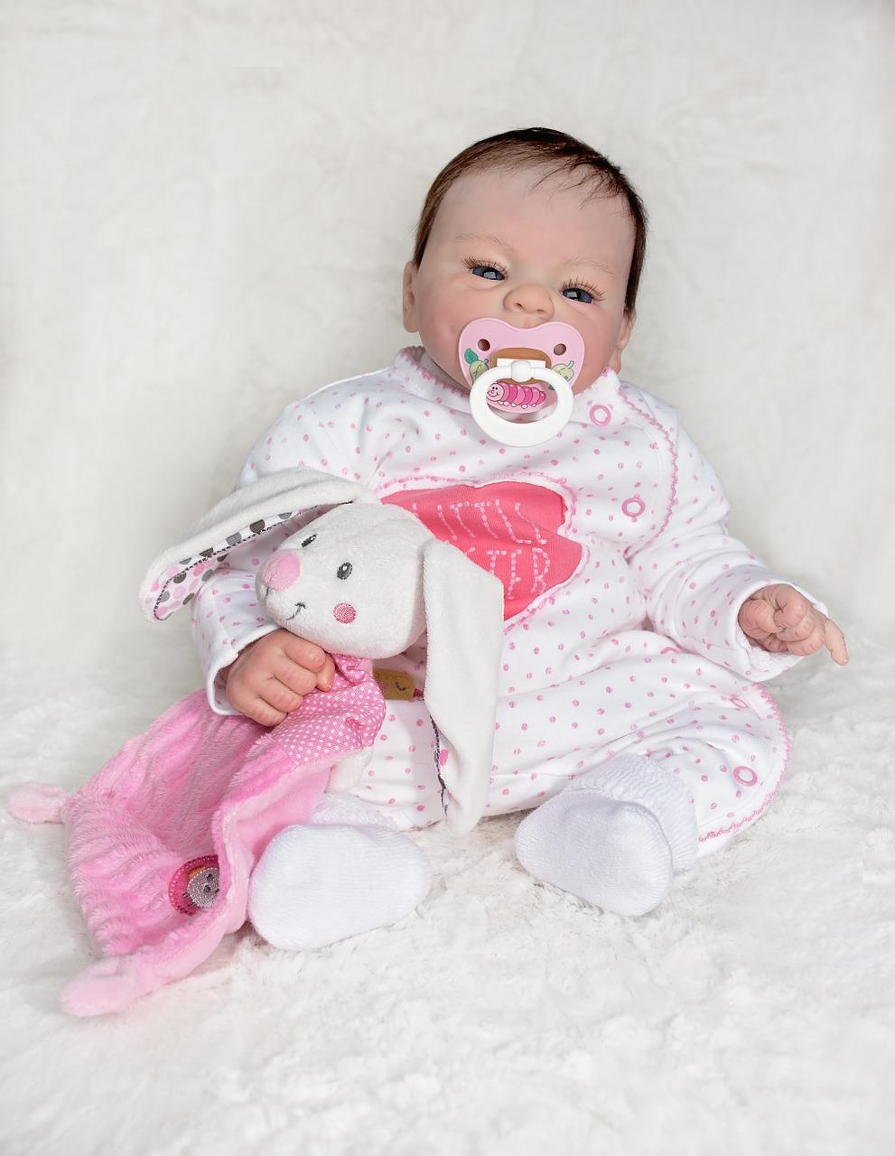 Ce bébé reborn a un doudou lapin rose.